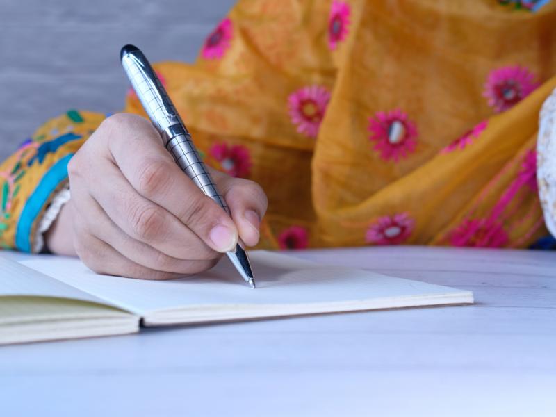 Kuvituskuva, kuvassa kynää pitelevä naisen käsi, käsi kirjoittaa paperille
